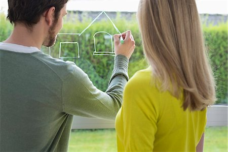 Woman looking at an architect drawing a design on the window glass Stock Photo - Premium Royalty-Free, Code: 6108-06166545