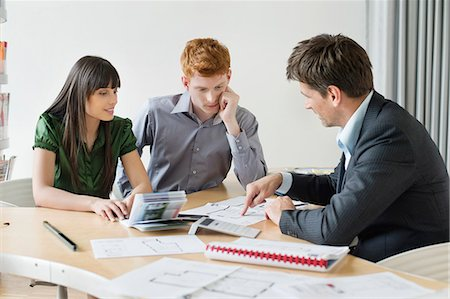 Real estate agent discussing property documents to his clients Stock Photo - Premium Royalty-Free, Code: 6108-06166549