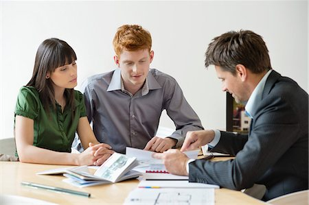 Real estate agent discussing property documents to his clients Stock Photo - Premium Royalty-Free, Code: 6108-06166556
