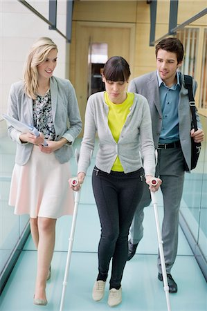 Disable woman walking with business executives in an office corridor Stock Photo - Premium Royalty-Free, Code: 6108-06166583