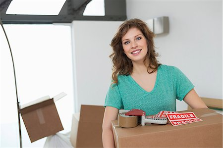 Woman carrying cardboard box and smiling Stock Photo - Premium Royalty-Free, Code: 6108-06166521