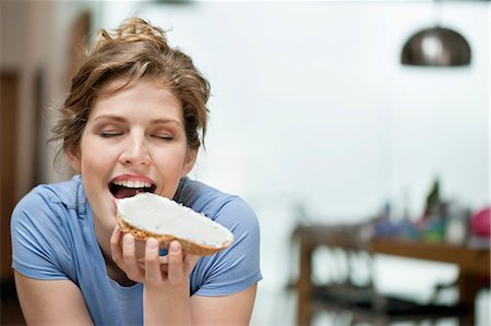 eating - Woman eating toast with cream spread on it Stock Photo - Premium Royalty-Free, Code: 6108-06166641