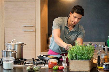 Man preparing food in the kitchen Stock Photo - Premium Royalty-Free, Code: 6108-06166644