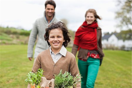 farm and boys - Portrait of a boy holding a basket of vegetables with his parents in a farm Stock Photo - Premium Royalty-Free, Code: 6108-06166668