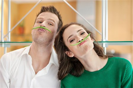 Couple playing with green bean in the kitchen Stock Photo - Premium Royalty-Free, Code: 6108-06166677