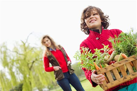 farm and boys - Boy holding a crate of assorted vegetables with his mother in a farm Stock Photo - Premium Royalty-Free, Code: 6108-06166681