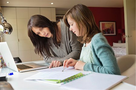 Girl studying with her mother at home Stock Photo - Premium Royalty-Free, Code: 6108-06166631