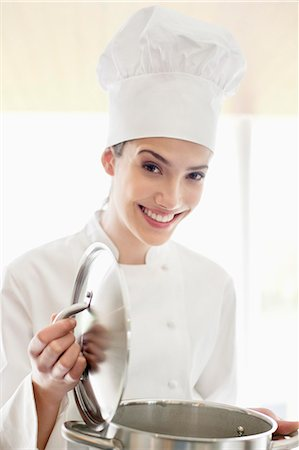 Happy female chef holding a saucepan Stock Photo - Premium Royalty-Free, Code: 6108-06166760