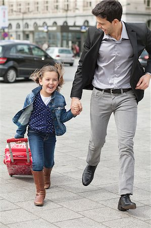 Girl pulling a trolley bag while running with her father Stock Photo - Premium Royalty-Free, Code: 6108-06166796