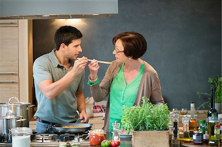 Man asking his mother to taste his cooking Stock Photo - Premium Royalty-Free, Code: 6108-06166706