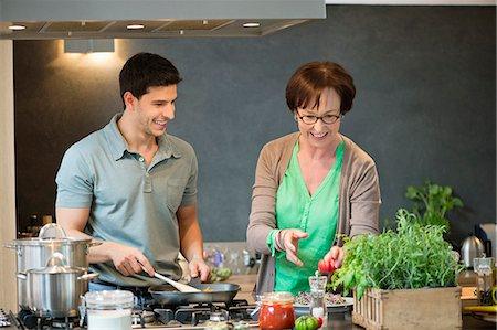 Woman assisting her son to cook food in the kitchen Stock Photo - Premium Royalty-Free, Code: 6108-06166715