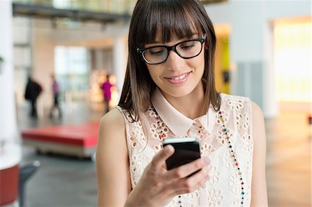 Businesswoman text messaging in an office Stock Photo - Premium Royalty-Free, Code: 6108-06166859