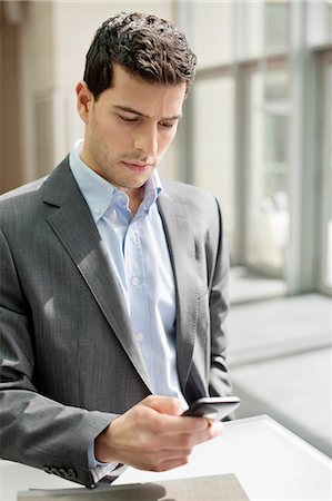 Close-up of a businessman text messaging Stock Photo - Premium Royalty-Free, Code: 6108-06166867