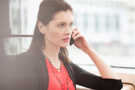 Woman traveling in a bus and talking on a mobile phone Stock Photo - Premium Royalty-Free, Code: 6108-06166877