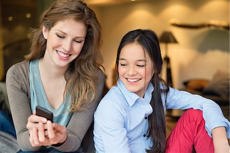 preteen beauty - Woman with her daughter using a mobile phone and smiling Stock Photo - Premium Royalty-Free, Code: 6108-06166886
