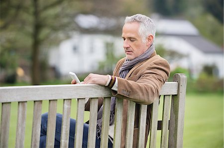 people sitting on bench - Man text messaging on a mobile phone in a park Stock Photo - Premium Royalty-Free, Code: 6108-06166898
