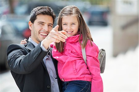 finger - Man carrying his daughter and pointing with finger Stock Photo - Premium Royalty-Free, Code: 6108-06166808