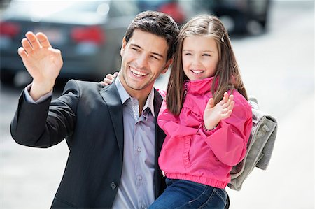 Man and his daughter waving hands Stock Photo - Premium Royalty-Free, Code: 6108-06166829