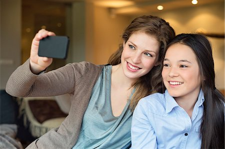 Woman and her daughter taking a picture of themselves with a camera phone Stock Photo - Premium Royalty-Free, Code: 6108-06166946