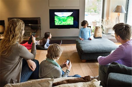 preteen family - Family using electronic gadgets in a living room Stock Photo - Premium Royalty-Free, Code: 6108-06166952