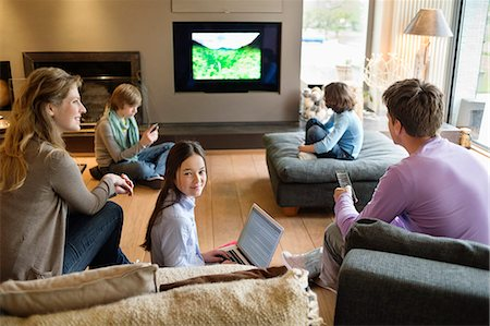 Family using electronic gadgets in a living room Stock Photo - Premium Royalty-Free, Code: 6108-06166957