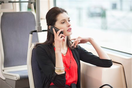 Woman traveling in a bus and talking on a mobile phone Stock Photo - Premium Royalty-Free, Code: 6108-06166967