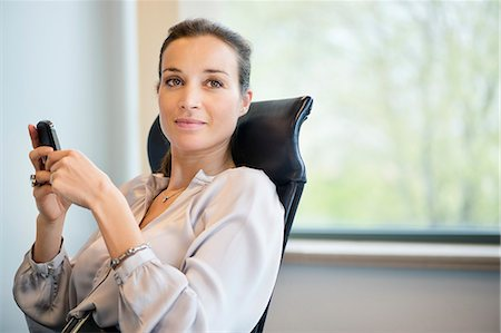 Portrait of a businesswoman text messaging on a mobile phone in an office Stock Photo - Premium Royalty-Free, Code: 6108-06166910