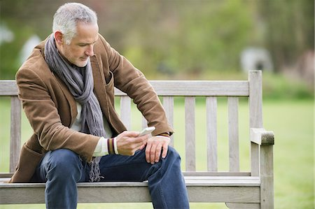Man text messaging on a mobile phone in a park Stock Photo - Premium Royalty-Free, Code: 6108-06166914