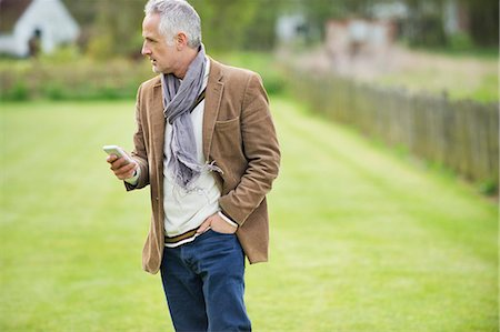 Man text messaging on a mobile phone in a lawn Stock Photo - Premium Royalty-Free, Code: 6108-06166919
