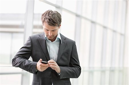 Businesswoman text messaging on a mobile phone in an office Stock Photo - Premium Royalty-Free, Code: 6108-06166920