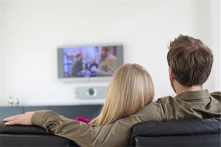 Rear view of a couple watching television Stock Photo - Premium Royalty-Free, Code: 6108-06166927
