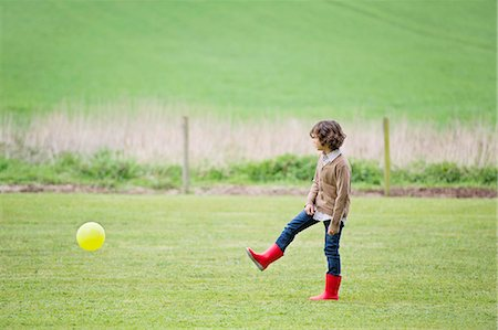 Boy playing with a ball in a field Stock Photo - Premium Royalty-Free, Code: 6108-06167009