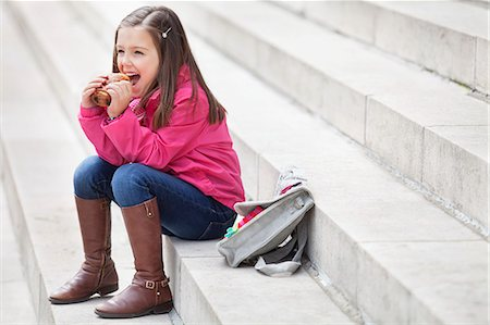 Schoolgirl sitting on the steps and eating pain au chocolat Stock Photo - Premium Royalty-Free, Code: 6108-06167021