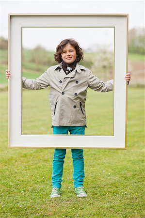 rectangle - Portrait of a boy standing with a frame in a park Stock Photo - Premium Royalty-Free, Code: 6108-06167035