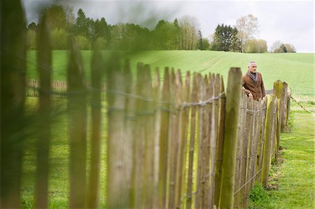 Man standing by fence in a field Stock Photo - Premium Royalty-Free, Code: 6108-06167141