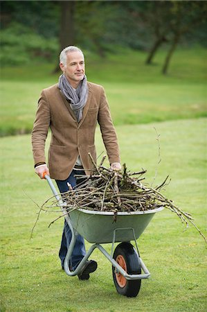 Man collecting firewood in a park Stock Photo - Premium Royalty-Free, Code: 6108-06167173