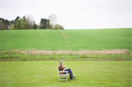 Man sitting on the bench and using a mobile phone in a field Stock Photo - Premium Royalty-Free, Code: 6108-06167177