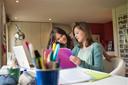 Girl studying with her mother at home Stock Photo - Premium Royalty-Free, Code: 6108-06167182