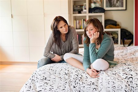 sad child sitting - Woman looking at her sad daughter in the bedroom Stock Photo - Premium Royalty-Free, Code: 6108-06167190
