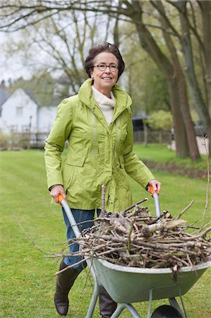 senior lady walking - Woman pushing a wheelbarrow full of branches Stock Photo - Premium Royalty-Free, Code: 6108-06167119