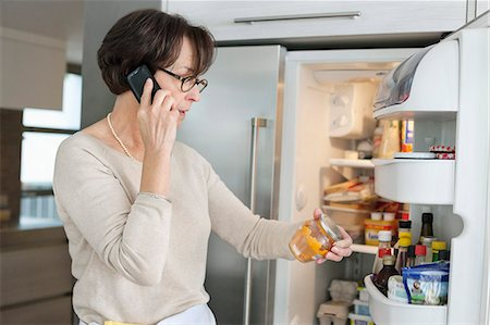 fridge - Elderly woman checking food items in a refrigerator and talking on a mobile phone Stock Photo - Premium Royalty-Free, Code: 6108-06167120