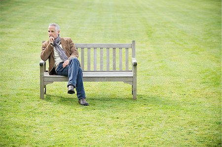 Man sitting on a bench and thinking in a park Stock Photo - Premium Royalty-Free, Code: 6108-06167139