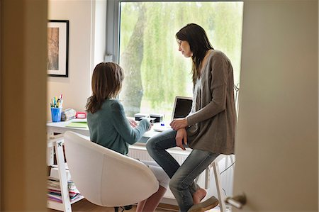 Girl studying with her mother at home Stock Photo - Premium Royalty-Free, Code: 6108-06167247