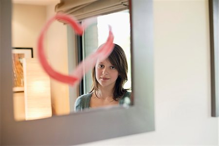 preteen beauty - Girl looking at reflection in mirror decorated with heart shape Stock Photo - Premium Royalty-Free, Code: 6108-06167285