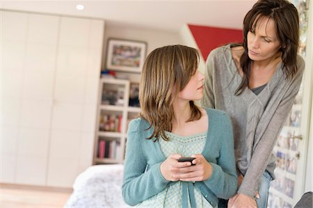 Girl text messaging on mobile phone and looking at her mother Stock Photo - Premium Royalty-Free, Code: 6108-06167202