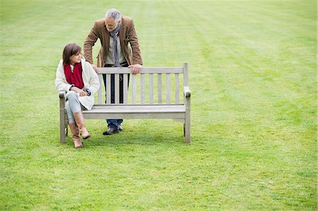 Man sitting with his daughter on a bench in a park Stock Photo - Premium Royalty-Free, Code: 6108-06167213
