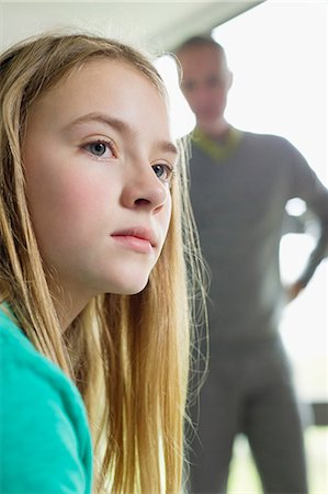 sad child sitting - Girl looking upset with her father standing beside her Stock Photo - Premium Royalty-Free, Code: 6108-06167222
