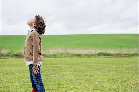 Boy daydreaming in a field Stock Photo - Premium Royalty-Free, Code: 6108-06167342