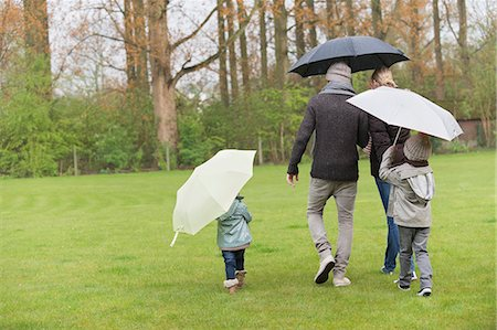 people with umbrellas in the rain - Family walking with umbrellas in a park Stock Photo - Premium Royalty-Free, Code: 6108-06167345