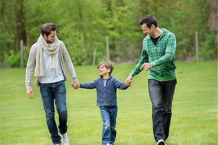 Boy walking with two men in a park Stock Photo - Premium Royalty-Free, Code: 6108-06167348